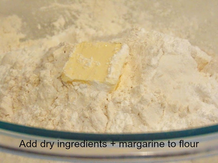 adding dry ingredients and margarine to flour